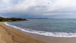 Empty peaceful golden sand beach on the French Riviera under an expressive overcast sky