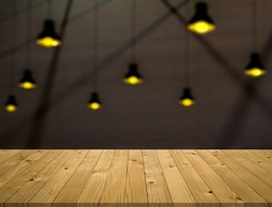 Empty perspective brown old plank wooden board mock up display shelf with abstract beautiful blurred low angle view warming light bokeh from electric ceiling lamp and yellow lighting background.