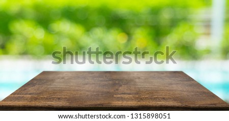 Empty perspective hard wood table and blurred hedge and swimming pool sunlight background. product display template.Business presentation #1315898051