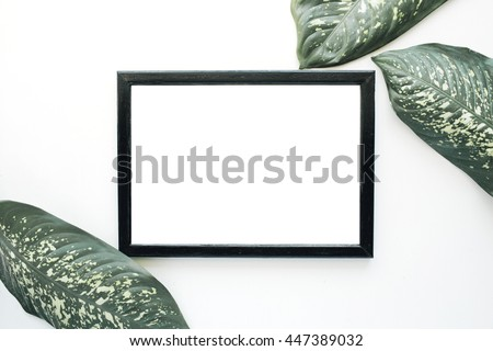Empty photo frame and green leaves isolated on white. flat lay, top view
