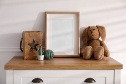 Empty photo frame near cute toy bunny and decor on dresser, space for text. Baby room interior element