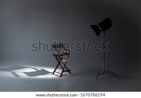 Empty photo studio with lighting equipment. Space for text. Vacant directors chair. The concept of selection and casting. Job recruitment advertisement.