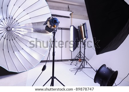 Empty photo studio with many modern lighting equipment; white backgrounds