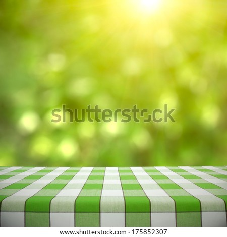 Empty picnic table on green foliage bokeh background
