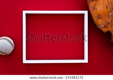 empty picture frame on a red wall with worn baseball glove and ball