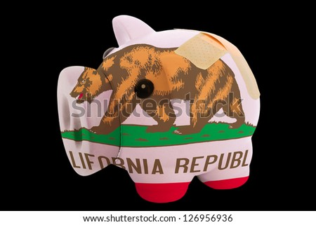 empty piggy rich bank in colors of flag of us state of california on black background