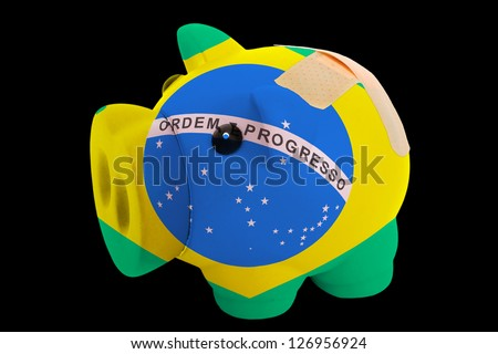 empty piggy rich bank in colors of national flag of brazil on black background