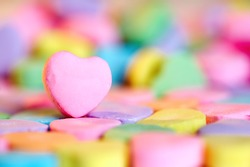 Empty pink heart candy over colorful bonbon