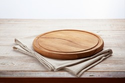 Empty pizza board and canvas tablecloth on white wooden deck. Selective focus.