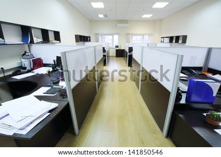 Empty places of work separated by partition with desktops and papers.