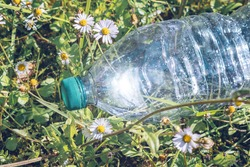 empty plastic water bottle amid flowery meadow with glowing sunlight reflection,pollution concept