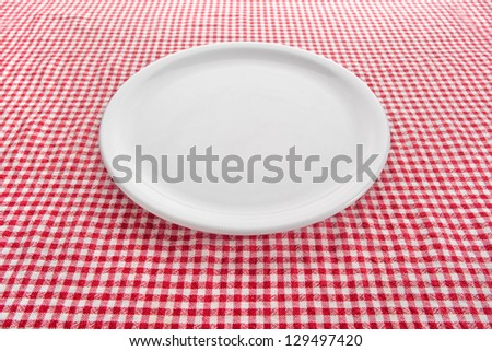 Empty plate. Empty white plate on kitchen table covered with checkered tablecloth.