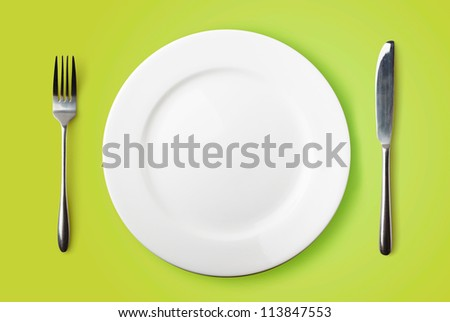 Empty plate, fork and knife on green background - stock photo