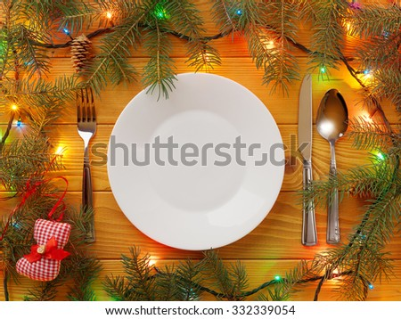 Empty Plate, fork, knife and spoon on wooden table. Christmas background