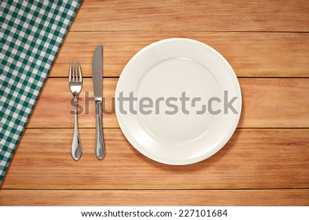 Empty Plate, Fork, Knife and Table Cloth on wooden background. Top View with Text Space