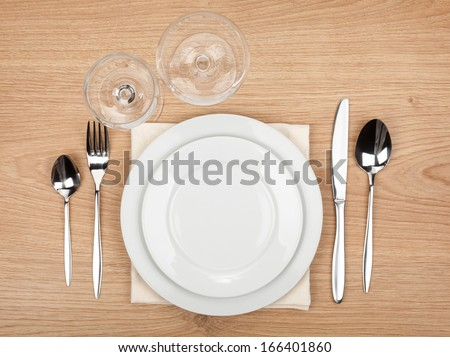 Empty plate, glasses and silverware set on wooden table
