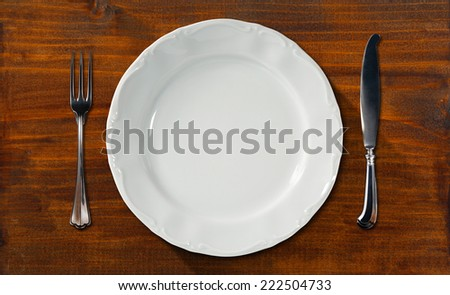 Empty Plate on Wooden Table with Cutlery / Empty and white plate on dark brown table with silver cutlery, fork and knife