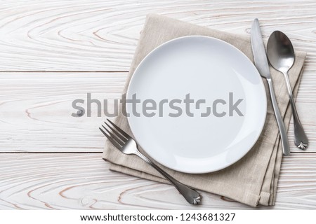 empty plate spoon fork and knife on table