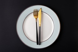 Empty plate with fork and knife at black background. Gold and black tableware with white plate at dark. Top view, flat lay