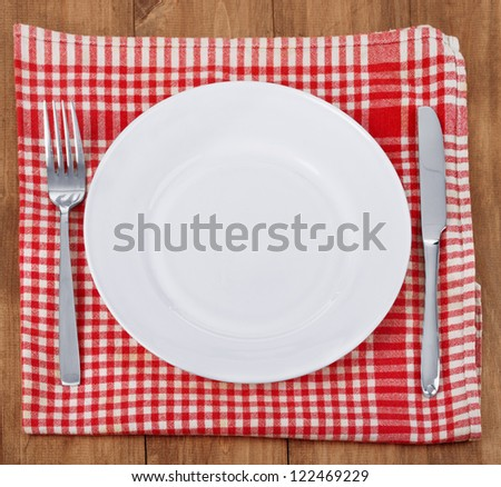 Empty plate with fork and knife on a red checked tablecloth on wooden table