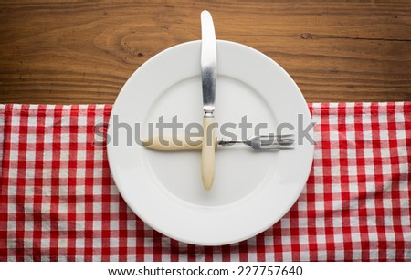 Empty plate with fork and knife on tablecloth over wooden background #227757640