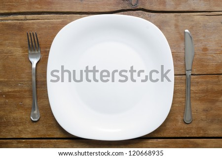 empty plate with fork and knife on the vintage wooden table