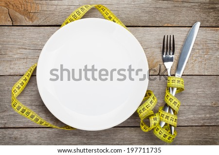 Empty plate with measure tape, knife and fork. Diet food on wooden table Сток-фото ©
