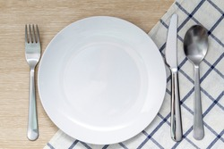 Empty plate with napkin and silverware over wooden table