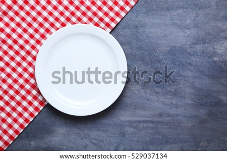 Empty plate with napkin on grey wooden table