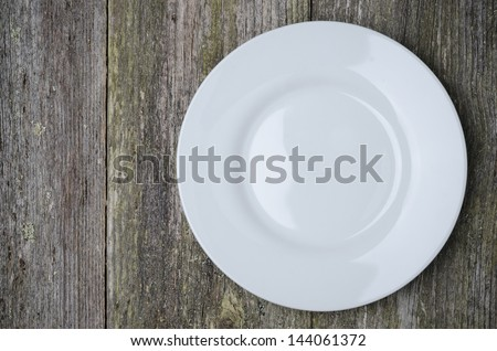 empty plate with space for text on old wooden background, horizontal close-up