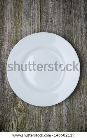 empty plate with space for text on old wooden background, vertical