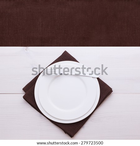 Empty plates and cutlery on table cloth on wooden table for dinner, menu in restaurant Top view square. Flat mock up for design.