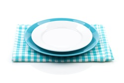 Empty plates over kitchen towel. Isolated on white background