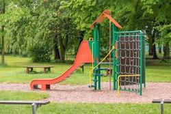 Empty playground after rain. Slide got wet in raindrops. Summer or spring rainy day. No people. No children.