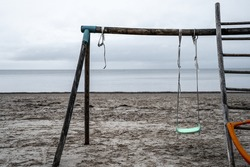 empty playground by the sea. lonely swing. atmosphere of abandonment and emptiness. seascape