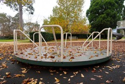 Empty playground roundabout surrounded by fallen autumn leaves in park.