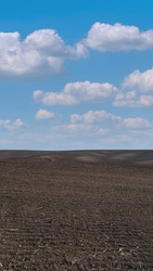 Empty plowed field under blue sky. Minimalistic and clean farming land for a banner background in vertical format. For agriculture industry