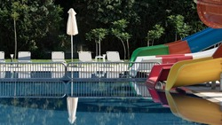 Empty pool area with slide, lounger and umbrella in seaside resort hotel. Exterior of hotel entertainment area. Holidays, vacations, travel, hospitality industry and tourism business