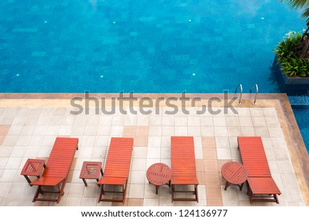 empty poolside deckchairs with beautiful blue swimming pool