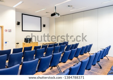 Empty presentation room with rows of blue seats, a white projection screen, a video projector on the ceiling, a computer screen on a desk and white walls.