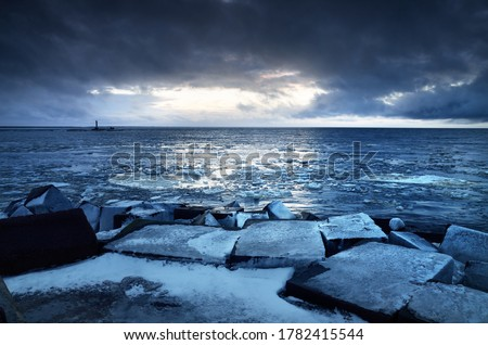 Photo of  Empty promenade and snow-covered breakwaters close-up. Lighthouse in the background. Baltic sea, Latvia. Dark storm clouds. Winter, seasons, climate change, global warming concepts. Long exposure
