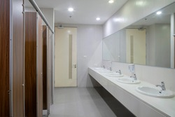 Empty public bathroom with lavatory and wide wall mirror, concept for public toilets.