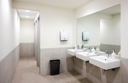Empty public bathroom with white sinks and wide wall mirror, air hand drier and black recycle bin