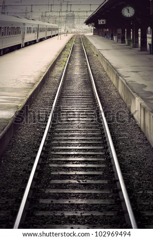 Empty railway track between platforms at train station