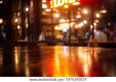 Empty real wood table top with light reflection on scene at restaurant, pub or bar at night. Blurred background for product display or montage your products with several concept idea and any occasion.