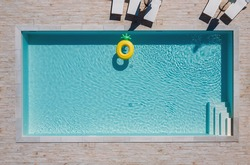Empty rectangular blue swimming pool with sunbeds and umbrellas and big inflatable Yellow Pineapple floating tube. Rent a real estate or Chill out summer vacation in luxury resorts concept.