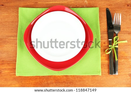 Empty red and white plates with fork and knife on wooden table, close-up