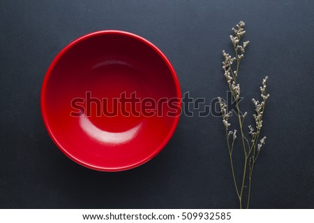 Empty red bowl and Flowers Dried on black background