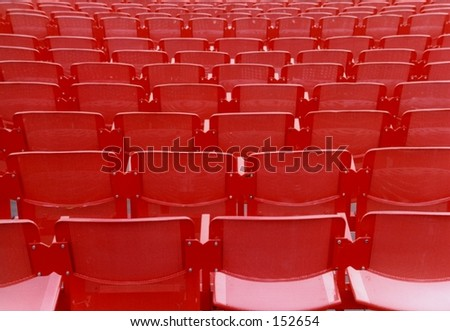 Empty red chairs in Arena concert hall - stock photo