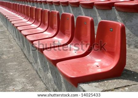 Empty red chairs in open-air arena
